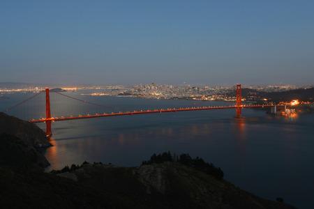 the back gate: Golden Gate Bridge at night, with San Francisco city skyline at back ground, San Francisco, California, USA Stock Photo