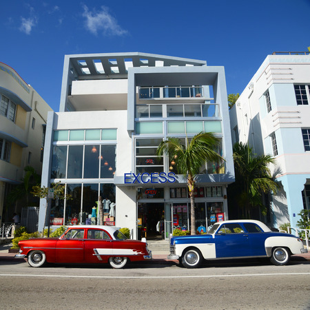 excess: Art Deco Style Building Excess and colorful antique cars in Miami Beach, Miami, Florida, USA.