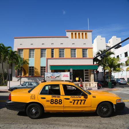 Art Deco Style Building Viscay Hotel and yellow cab on Collins Avenue in Miami Beach, Miami, Florida, USA.