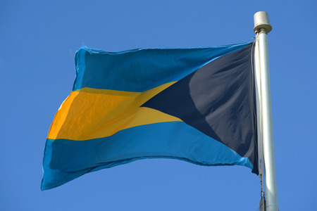 gained: Flag of Bahamas waving against blue sky. It has been the flag of the Commonwealth of the Bahamas since the country gained independence in 1973. Stock Photo