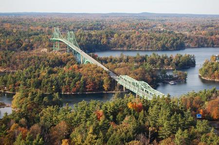 Puente de las mil islas a través del río San Lorenzo. Este puente conecta el estado de Nueva York en los Estados Unidos y Ontario en Canadá, cerca de las Mil Islas. Foto de archivo - 87403278