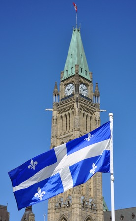 Quebec Flag with Bourbon Lilies flying in front of Peace Tower, Parliament Hill, Ottawa, Canada. Photo Focus on the flag.