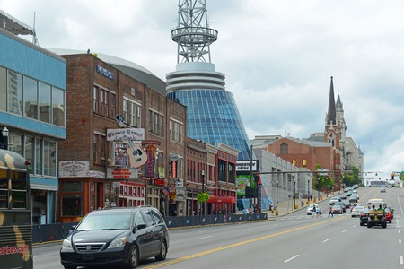 Bars and Bridgestone Arena on historical Broadway in downtown Nashville, Tennessee, USA. Lower Broadway is famous for entertainment district of country music.