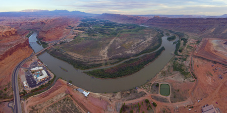 Aerial view of Colorado River and La Sal Mountains panorama at sunset near Arches National Park in Moab, Utah, USA.