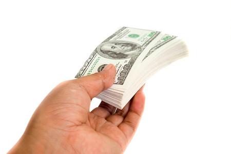 A hand handing over stack of one hundred dollar bills isolated on white background. High resolution product. Close up