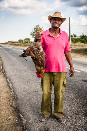 TRINIDAD, CUBA - FEBRUARY 11  An unidentified man sells live rooster on the road between Trinidad and Sancti Spiritus ond February 11, 2011