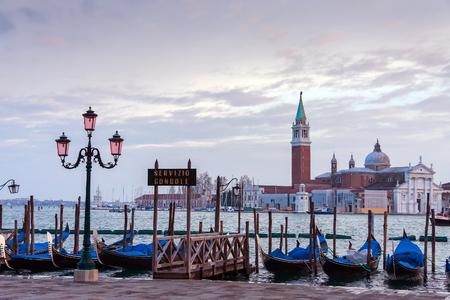 ゴンドラの行は、スキアヴォーニ、ヴェネツィア、イタリアでの横にある駐車。ヴェネツィアのラグーンの眺め。同じ名前の島にサン ・ ジョルジョ 写真素材