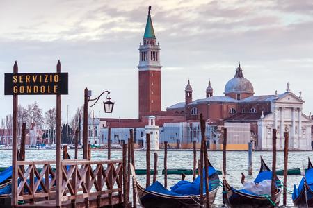 ゴンドラの行は、スキアヴォーニ、ヴェネツィア、イタリアでの横にある駐車。ヴェネツィアのラグーンの眺め。同じ名前の島に San Giorgio マッジョ 写真素材