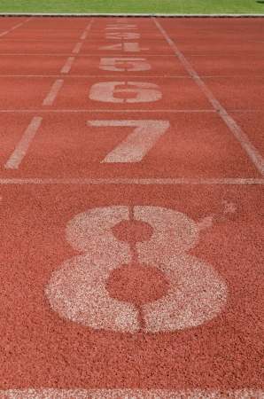 level playing field: number on running track finish line Stock Photo