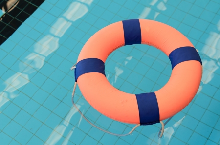grand strand: orange pool float, pool ring in cool blue refreshing blue pool, room for your text Stock Photo