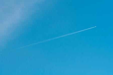 airplane flies in white clouds in a blue sky and leaving trail photo