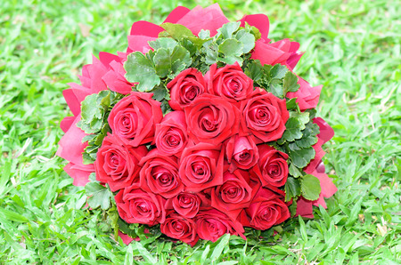 Bouquet of red roses on the grass