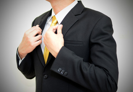 handsom: Asian handsom businessman wearing black suit correcting his suit. Stock Photo