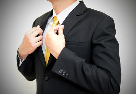 handsom: Empresario handsom asi�tica llevaba traje negro corregir su traje. Foto de archivo