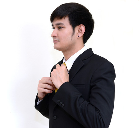 handsom: Asian handsom businessman wearing black suit correcting his tie. Stock Photo