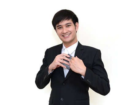 breast pocket: Handsome businessman reaching into his coat pocket to get his wallet. Stock Photo
