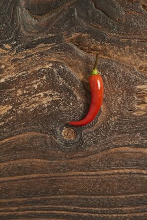 Red hot chili pepper on old wooden background.