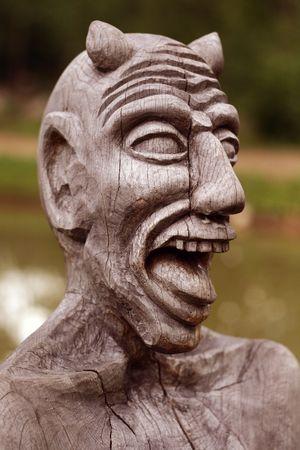 wooden devil head on green background