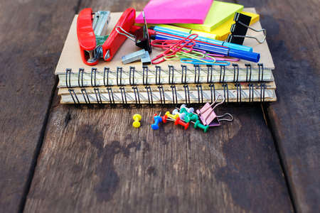 Notebook with school supplies on a old wood background Stock Photo