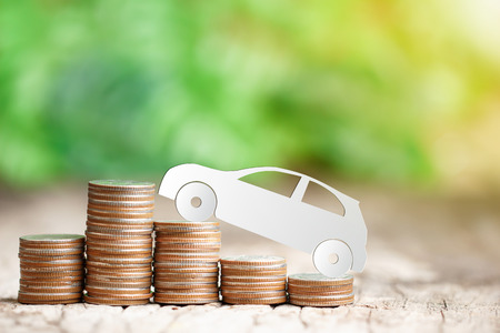 Paper eco car on coin stack, saving money for a car