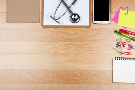 Office supplies and stethoscope on wooden table with copy space, top view