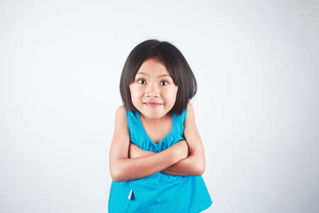 Cheerful little Asian girl excitement and funny face on gray background