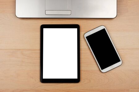 Tablet and smartphone with blank screen and laptop on wooden desk