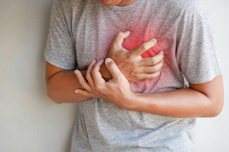 Closeup of a man pressing on chest with painful expression, heart disease. Healthcare and health problem concept Banque d'images