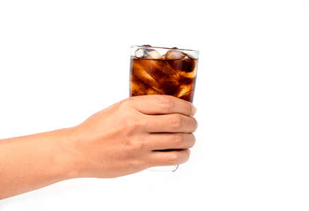 Hand holding a glass of cola with ice on white background