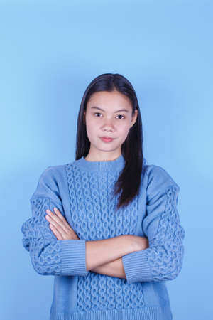 Young women cross one's arm wearing blue knitting sweater on blue background