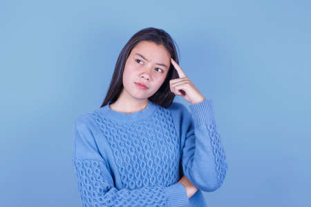 Young beautiful woman in a thoughtful on blue background 免版税图像
