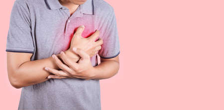 Closeup of a young man burning in the middle of the chest and stomach ache on pink background with copy space 免版税图像