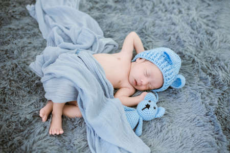 Portrait of twenty seven day old newborn asian baby boy in knitted blue hat with teddy bear is sleeping on blue fur bed in the studio