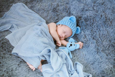 Portrait of twenty seven day old newborn asian baby boy in knitted blue hat with teddy bear sweet sleeping on blue fur bed in the studio Imagens