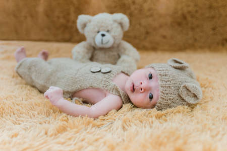 Portrait of twenty seven day old asian baby boy in knitted bear suit with hat and teddy bear sleeping on brown fur bed in the studio