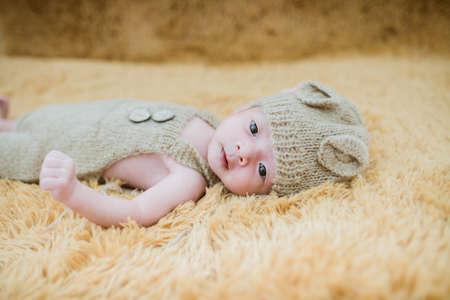 Portrait of twenty seven day old asian baby boy in knitted bear suit with hat sleeping on brown fur bed in the studio Imagens