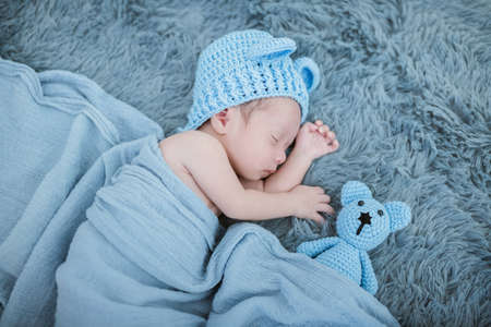 Portrait of twenty seven day old newborn asian baby boy sleeping on blue fur bed in the studio