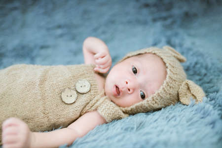 Portrait of twenty seven day old asian baby boy in knitted bear suit is sleeping on blue fur bed in the studio