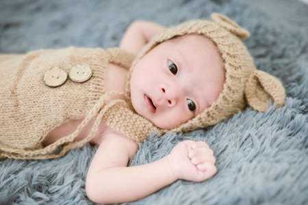 Portrait of twenty seven day old asian baby in knitted bear suit is sleeping on blue fur bed in the studio.  Happy baby boy looking at the camera Imagens