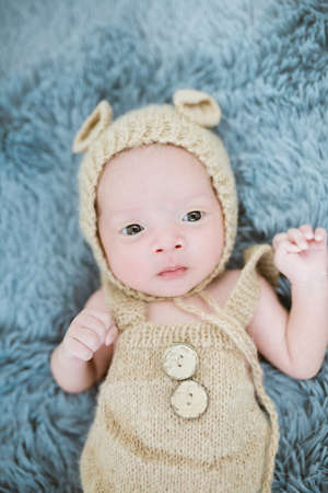 Portrait of twenty seven day old asian baby boy in knitted bear suit with hat sleeping on blue fur bed in the studio Imagens