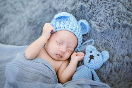 Portrait of twenty seven day old newborn asian baby boy in knitted blue hat with teddy bear sleeping on blue fur bed in the studio