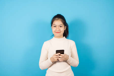 Portrait of Asian teenager wearing light pink sweater excited for success with arms raised isolated over blue background, strong successful Imagens