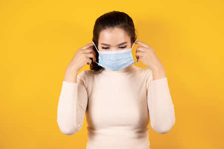 Portrait of Asian woman wearing medical face mask to protect Covid-19 (Coronavirus) on yellow background, people to stay home, health and medicine concept