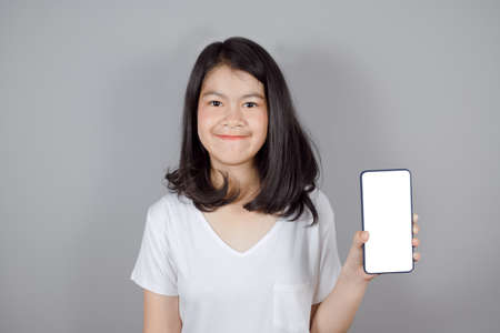 Portrait of Asian teenager  in medical face mask to protect Covid-19 (Coronavirus) wears white t-shirt standing crossed arms isolated on gray background , health and medicine concept Imagens