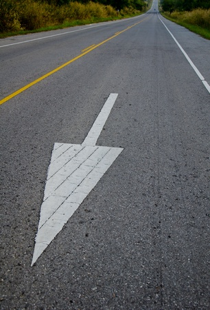 white arrows sign traffic on road photo
