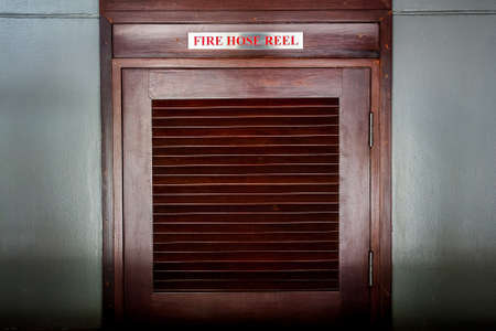 louvered: wooden door of fire hose reel cabinet Stock Photo