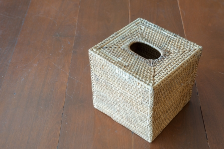 Tissue box of rattan basketry on wooden table photo