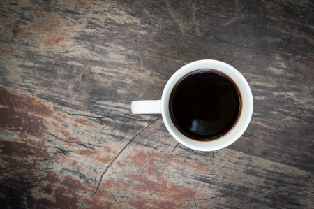 Hot Cup of Coffee on a grungy Wooden Table photo