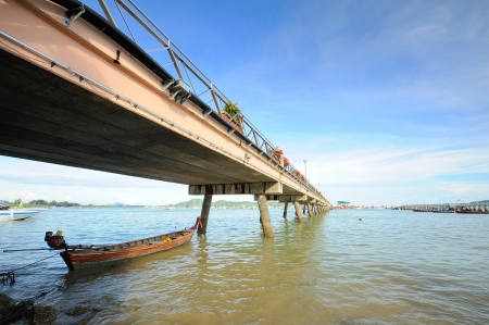 fisherman boat resting under the bridge in Andaman sea, Phuket Thailand Stock Photo - 16734106