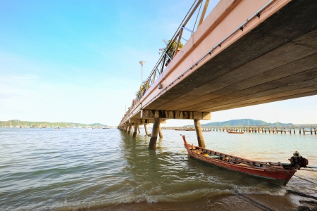 fisherman boat resting under the bridge in Andaman sea, Phuket Thailand Stock Photo - 16734108
